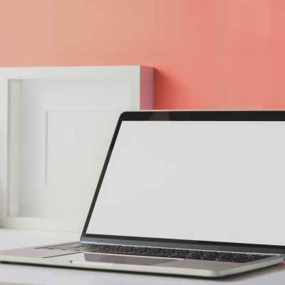 laptop beside peach color wall